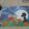 An image from Charles Shulz The Great Pumpkin comes to life on the pavement as created in chalk by illustrator and artist Eric Maruscak.