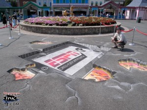 Artist and Illustrator Eric Maruscak works on a 3D chalk mural for ESPN XP Cross Platform marketing at the ESPN Summer Picnic held at Lake Compounce Amusement Park in Bristol, Connecticut.