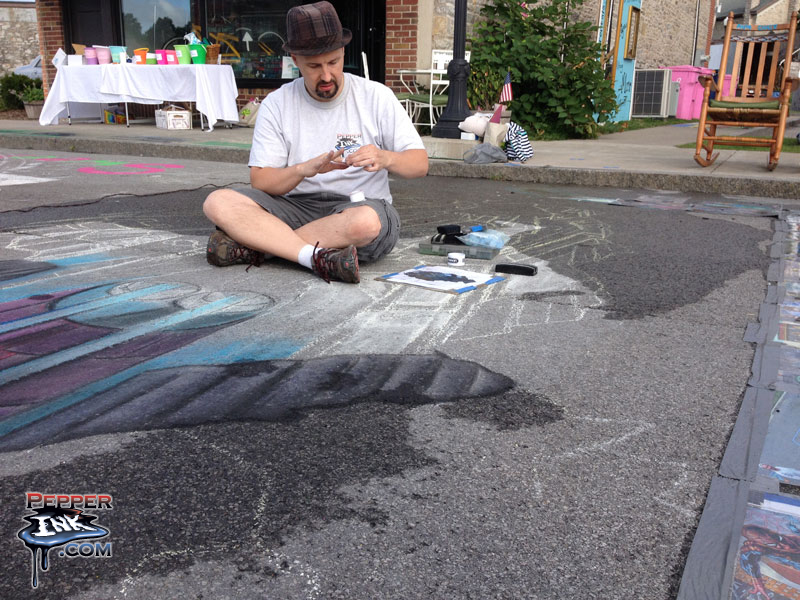 Eric Maruscak works on his 3D Batman chalk art as the pavement dries from overnight rain.